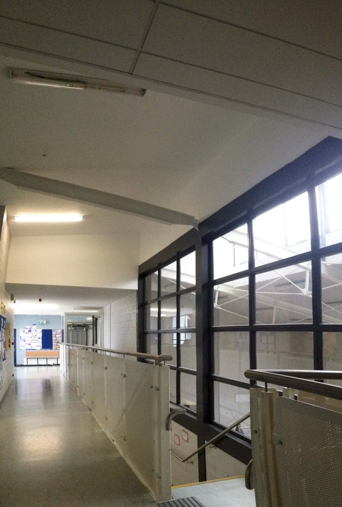 School corridor on first floor showing sports hall on right.